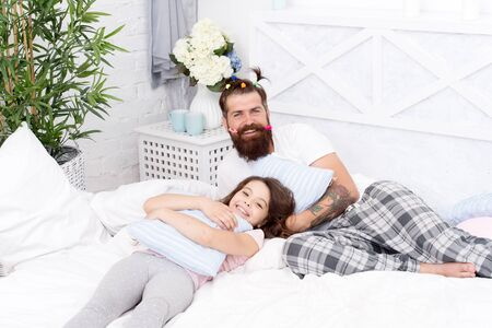 we are one. family bonding time. Relax sweetie. i love my daddy. happy morning together. funny pajama party. small girl with bearded father in bed. weekend at home. father and daughter having fun