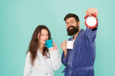 tea time at home. hard morning. morning couple drink coffee. Wife and husband bathrobe. bearded man and girl coffee cup. wake up time. family life routine. couple in love alarm clock. love relations 스톡 콘텐츠