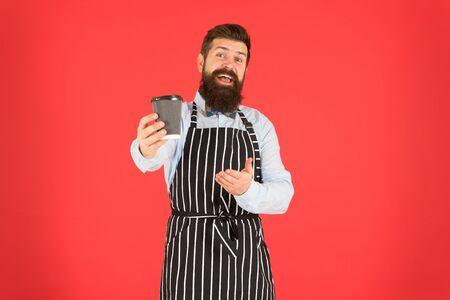 Esto es para ti. hombre barbudo mantenga el café para llevar. camarero brutal en el café. hombre maduro fondo rojo. criado habilidoso. Delantal de chef barista hipster. barman elegante y confiado. hombre bebe cafe