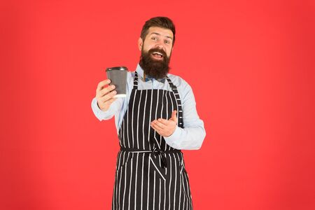this is for you. bearded man hold take away coffee. brutal waiter in cafe. mature man red background. skilled servant. barista hipster chef apron. elegant confident bartender. male drink coffee