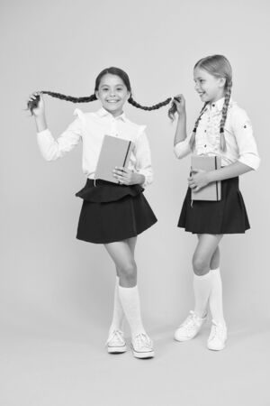 happy girls study with workbook. reading and writing. small girls kids with book. literature lesson. childrens literature. back to school. Classmates at book store or library. interesting book