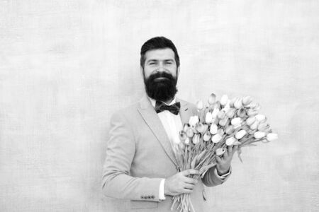 bearded man in bow tie with tulip flowers. bride groom at wedding party. spring bouquet. 8 of march. love date with flowers. Happy Birthday. womens day. Formal mature businessman. Forever young