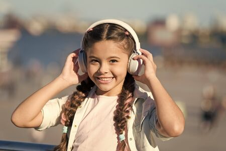 Exciting journeys through cities and museums. Audio tour headphones gadget. City guide and audio tour. Girl little tourist kid explore city using audio guide application. Free style of travelling Banco de Imagens
