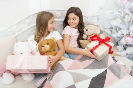 Opening presents on Christmas morning. New Year surprise. Happy small children hold gift boxes. Cute small girls with presents in bed. Wake up and have some fun. Merry Christmas and Happy New Year