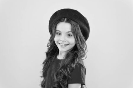 modern fashion style. childhood. hairdresser salon. little girl in french style hat. summer fashion and beauty. parisian child on yellow background. happy girl with long curly hair in beret