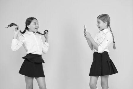 Social media marketing. Modern technology. Digital influencer. Little blogger. Blogger school. Schoolgirls use smartphone take photo.Life online. Application smartphone. Personal blog. Content making Banco de Imagens