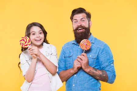 togetherness. Sweet childhood. Daughter and father eat sweet candies. bearded hipster man is good dad. daddy and small girl kid love colorful lollipop. summer vibes. happy family rest. health care