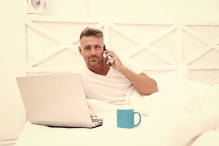 Online world. Man surfing internet work online. Already at work. Digital marketing. Remote access. Hipster bearded guy pajamas freelance worker relaxing at home. Remote work concept. Social networks 版權商用圖片