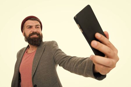 His best selfie is yet to come. Bearded man smiling to selfie camera. Happy hipster taking selfie with smartphone in hand. Perfect selfie from any angle Stockfoto
