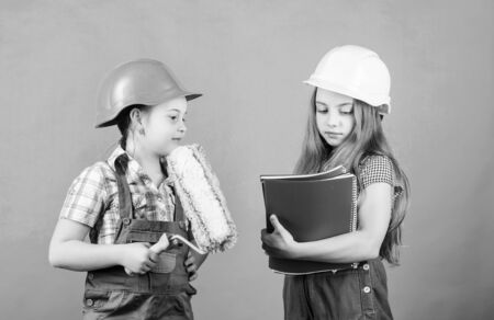 Labor day. 1 may. Foreman inspector. Repair. school project. small girls repairing together in workshop. Little kids in helmet with tablet and roller. Labor day concept. Labor day for children