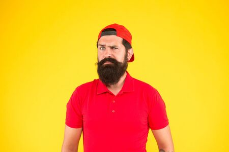 Barber salon and facial hair care. being trendy and brutal. Beard and mustache grooming. sad mature hipster yellow background. bearded man red shirt and cap. male summer fashion. Shampoo for men