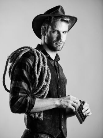 wet your whistle. wild west rodeo. man in hat drink whiskey. man checkered shirt on ranch. western cowboy portrait. Vintage style man. Wild West retro cowboy. cowboy with lasso rope. Western Stockfoto
