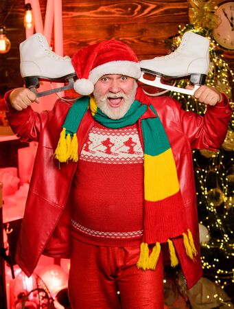 Be active. Santa Claus grandfather hold figure skates. Bearded man with pair of skates. Skater christmas gift. Winter fun christmas holidays. Winter sports. Winter leisure. Elderly people fun Imagens - 134386223