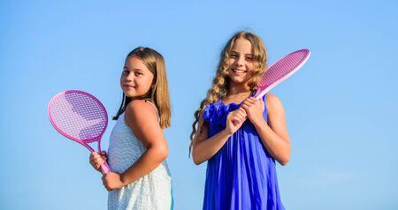 永不止步。夏季体育活动。精力充沛的孩子。快乐而开朗。运动型游戏玩。夏季户外游戏。打网球。童年幸福和姐妹情谊。有网球拍的小女孩