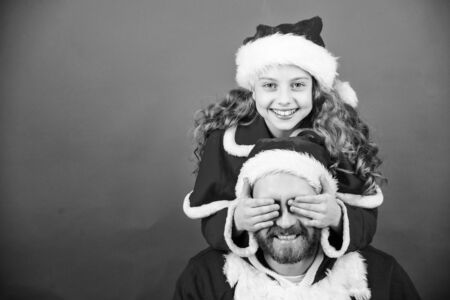 My dad is santa claus. Belief in santa constitutes most magical part of childhood. Guess who. Surprise concept. Girl child and bearded father wear santa costume. How to be santa claus parents guide Banco de Imagens