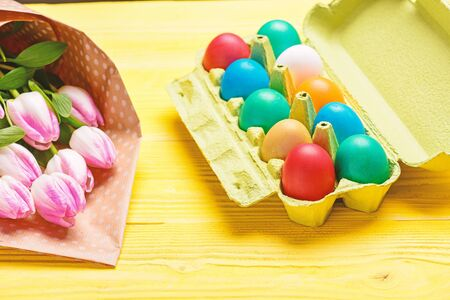 Spring holiday. Holiday celebration, preparation. Egg hunt. painted eggs in egg tray. Tulip flower bouquet. Healthy and happy holiday. Happy easter. Organic Easter Zdjęcie Seryjne