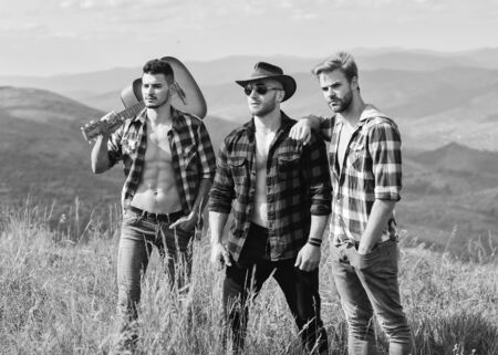 Men with guitar hiking on sunny day. Group of young people in checkered shirts walking together on top of mountain. Long route. Adventurers squad. Tourists hiking concept. Hiking with friends