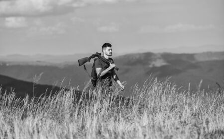 Regulation of hunting. Hunter hold rifle. Nice day for hunt. Hunter spend leisure hunting. Walking in mountains. Hunting masculine hobby concept. Man brutal gamekeeper nature landscape background