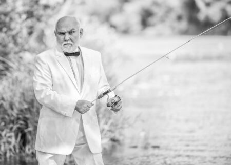 hobby and recreation. Fishermen in formal suit. successful catch. business success. mature man fishing. fisher celebrate retirement. good production. retired businessman. Good profit. formal fashion