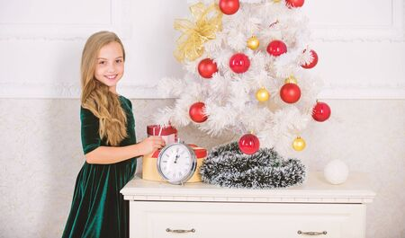 Last preparations. Child celebrate christmas at home. Favorite day of the year. Christmas celebration. Get incredibly excited about christmas. Kid girl near christmas tree waiting midnight clock