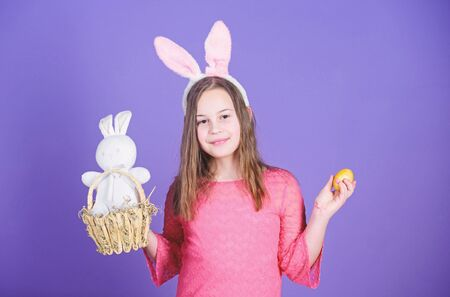 Easter egg hunts as part of festival. Girl little child easter bunny accessory hold dyed egg. Origin of easter bunny. Easter symbols and traditions. Playful child with soft toy. Meet spring holiday