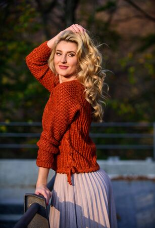 Autumn stylish outfit. Fall fashion. Adorable lady enjoy sunny autumn. Woman walk in autumn park. Cozy knitwear. Knitted sweater. Fashionable clothes. Girl gorgeous blonde. Femininity and tenderness Zdjęcie Seryjne