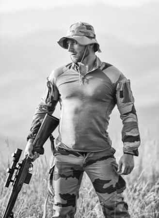 Brutal warrior. Rifle for hunting. Hunter hold rifle. Hunter mountains landscape background. Army forces. Man military clothes with weapon. Ready to shoot. Focus and concentration experienced hunter