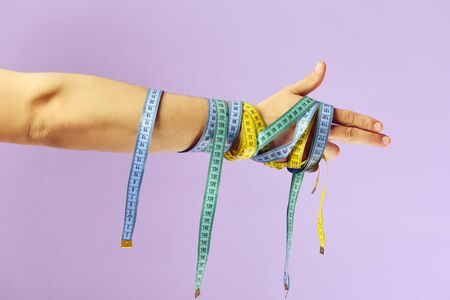 Hand with flexible rulers on light purple background. Mans wrist pretending to be gun wrapped with yellow and cyan tapes for measuring. Weight management idea. Fitness, regime and diet concept