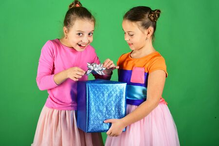 Girls with tricky faces pose with present on green background