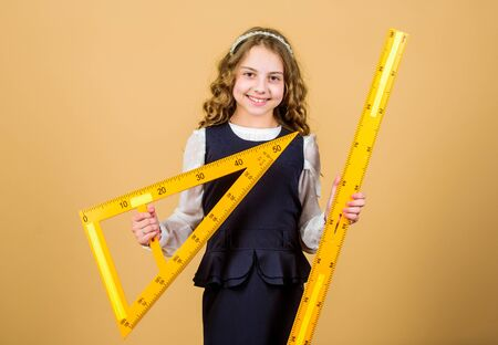Education and school concept. Smart and clever concept. Sizing and measuring. School student study geometry. Kid school uniform hold ruler. Pupil cute girl with big ruler. Geometry school subject Banque d'images