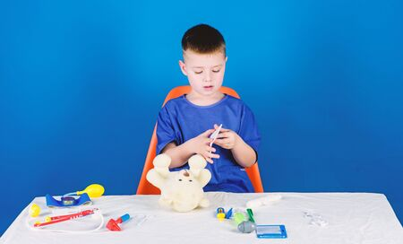 Hospital worker. Health care. Kid little doctor busy sit table with medical tools. Medical examination. Medicine concept. Medical procedures for teddy bear. Boy cute child future doctor career