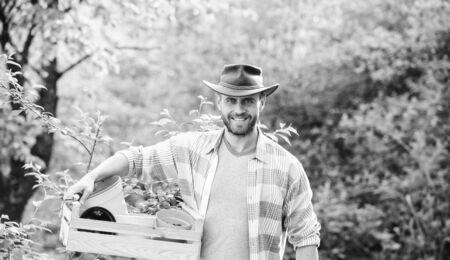 农夫拿着有罐的木箱。生态农场工人。收成。地球节快乐。生态生活。农业和农业栽培。园林装备。牛仔帽的肌肉牧场人。我喜欢我的工作