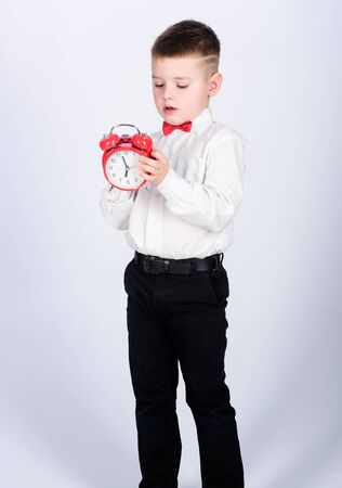 happy child with retro clock in bow tie. Party time. Businessman. Formal wear. Time management. Morning. little boy with alarm clock. Time to relax. tuxedo kid. Happy childhood. Good start of morning Stockfoto