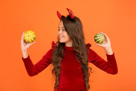 Creepy crawly. Happy little girl hold pumpkins orange background. Small child dressed up as creepy devil. Creepy look will freak out all your friends. Creepy and scary. Halloween celebration Reklamní fotografie