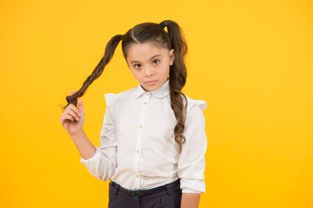 Curly hair ponytails for back to school. Adorable small girl twisting hair around her finger on yellow background. Cute little child with long brunette hair. Styling hair for school