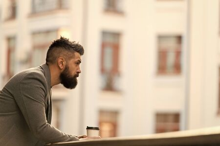 Businessman well groomed appearance enjoy coffee break out of business center urban background. Relax and recharge. Man bearded hipster drink coffee paper cup. One more sip of coffee. City lifestyle Stock fotó
