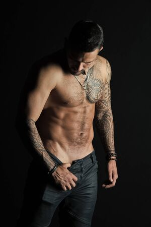 Man stripper show sexy torso. Sportsman with six pack and ab stripping. Athlete with biceps and triceps muscles. Fashion man with tattoo take off jeans. Desire with sexuality and attraction