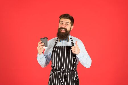 best taste ever. elegant confident bartender. male drink coffee. bearded man hold take away coffee. brutal waiter in cafe. mature man red background. skilled servant. barista hipster chef apron