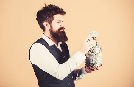 Safe place to keep money. Personal accountant. Businessman with his dollar savings. Richness and wellbeing. Man bearded guy hold jar full of cash savings. Security and money savings. Banking concept