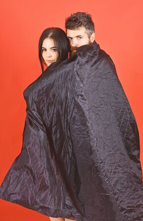 Vampire in cloak behind devil girl. Man and woman dressed like vampire, demon, red background. Couple in love relations, perfect match. Girl on calm face, covered with cloak. Devil love concept.