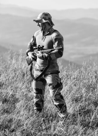 Army forces. Ready to shoot. Hunter hold rifle. Hunter mountains landscape background. Focus and concentration experienced hunter. Man military clothes with weapon. Brutal warrior. Rifle for hunting