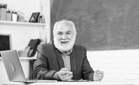 Talking to students or pupils. Senior school teacher concept. Honored professor. Teacher bearded man tell cheerful story. Teacher charismatic grandpa sit at table classroom chalkboard background