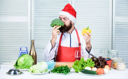 Healthy christmas holiday recipes. How make your christmas dinner healthier. Man bearded chef wear santa claus hat cooking. How to enjoy holiday meals. Enjoy healthy christmas dinner. Christmas diet