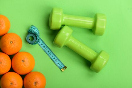 Oranges near dumbbells, cyan measuring tape on green background,