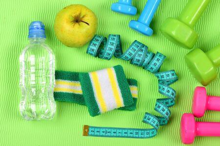 Dumbbells, apple, water bottle and cyan measure tape 版權商用圖片