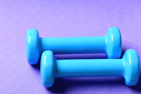 Barbells made of plastic, close up. Dumbbells in cyan color