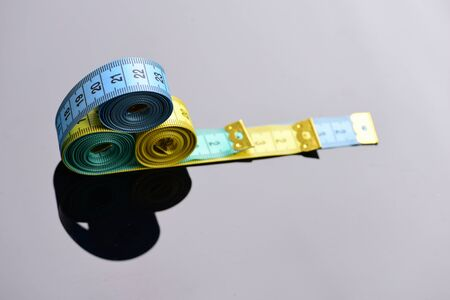 Measuring tape rolls placed on each other on mirror background