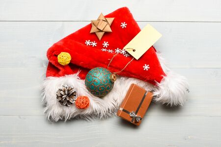 Christmas presents from santa. Pay attention to details. Attributes of winter holidays. New year and christmas decorations. Santa hat white background top view. Santa hat with christmas gift box 版權商用圖片