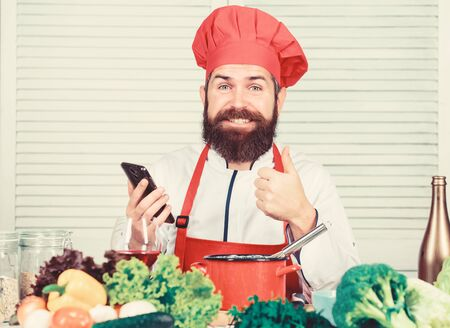 Culinary school. Hipster in hat and apron learning how cook online. Culinary education online. Elearning concept. Man chef searching internet recipe cooking food. Chef smartphone watch culinary show