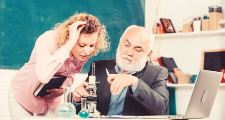 Teacher and girl with notepad near chalkboard. Biology science. Study biology. College university education. Biologist or chemist with microscope teaching student biology. Biological research Foto de archivo - 134843086